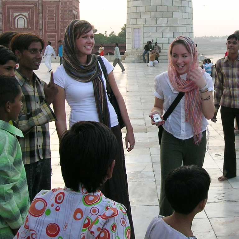 Two female students talk with young children in India
