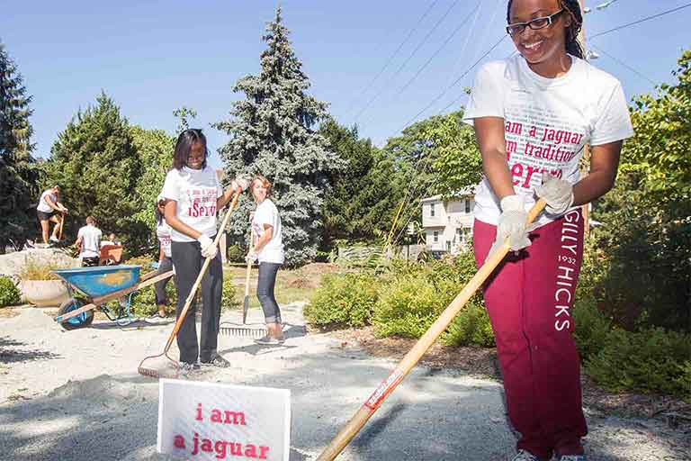IUPUI student volunteers spreading gravel with rakes for iServe day