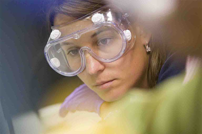 Close-up of a female IUPUI student wearing goggles in a lab environment