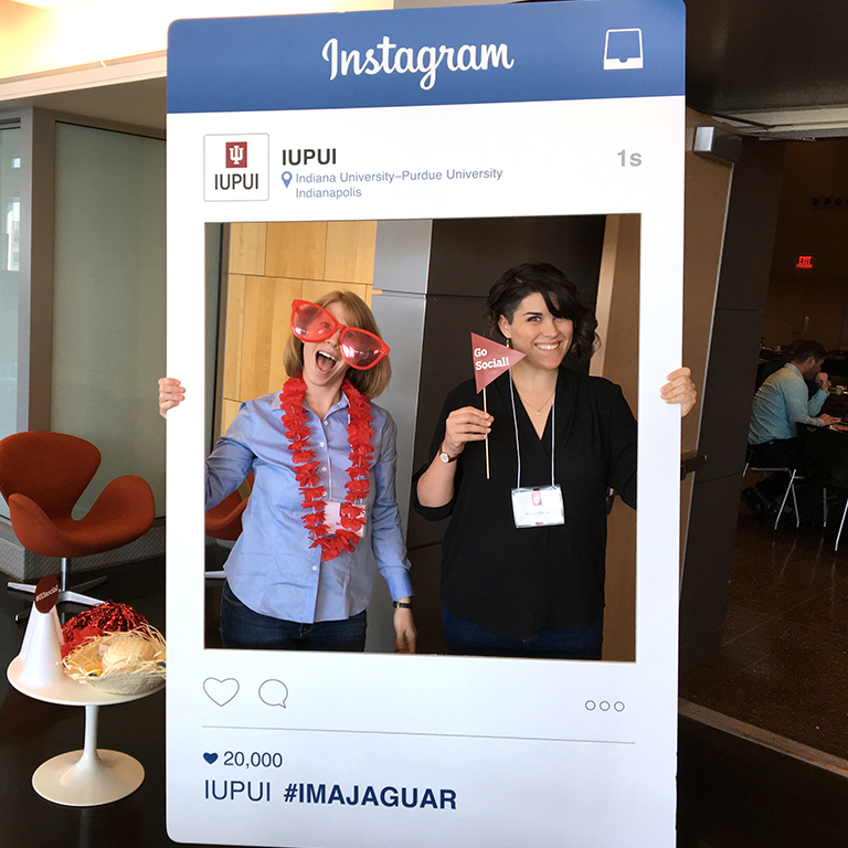 Photo of past attendees posing in an Instagram cardboard cutout.