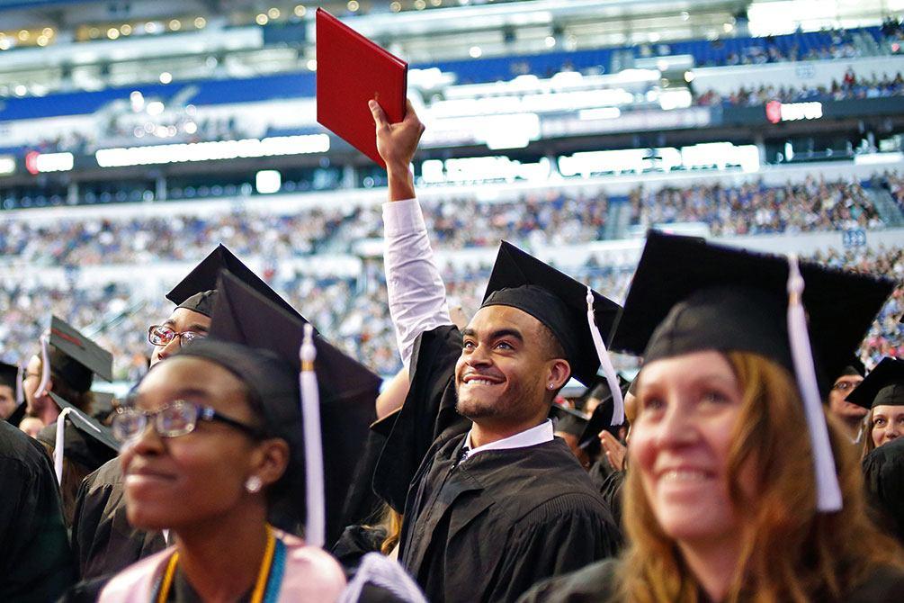 IUPUI graduate holds up diploma