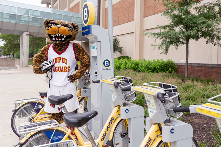 IUPUI mascot Jawz holds a bike helmet while standing near a shared bike station.