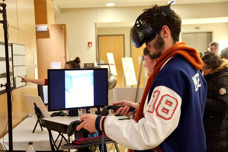 A student uses a virtual reality headset at the Capstone event.