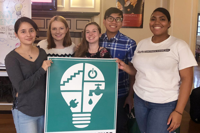 Five smiling students hold an energy challenge banner.