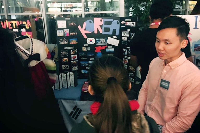 IUPUI student Jaeyho Yu talks to another student in front of a display about Korea.