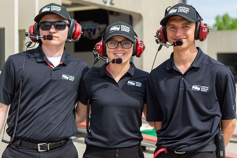 Owen Gilliland, Amelia Jakubec and Isaac Atkinson with headsets on at the Indianapolis Motor Speedway.