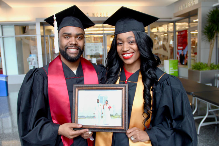 Ronae Williams and Ralph Durrett Jr. hold their wedding photo as they stand in their caps and gowns before Commencement.