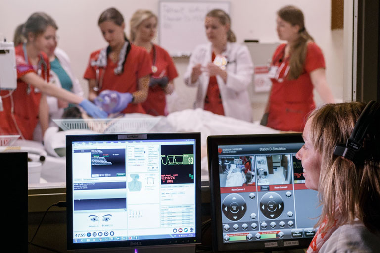 A computer screen showing medical information in front of a group of nursing students working on a patient.