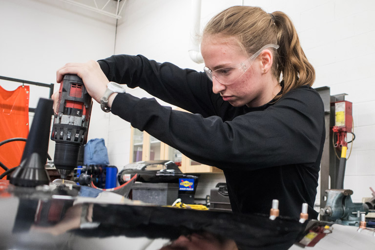 A student works on a car.