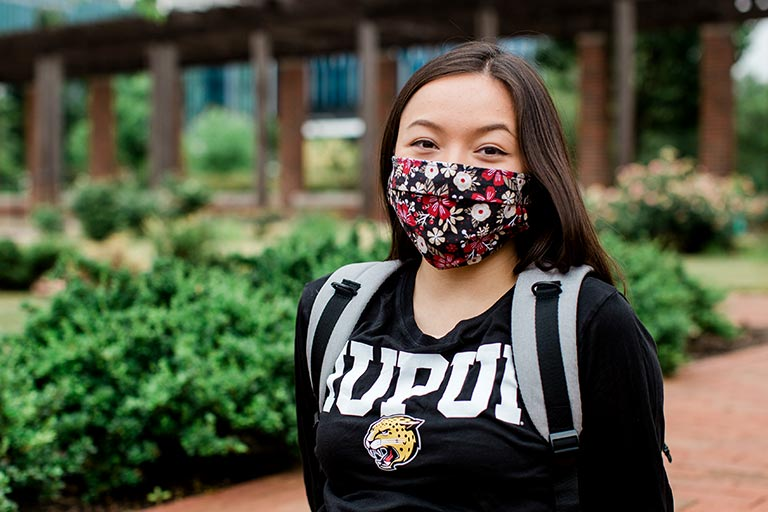 A girl relaxes on campus with a mask covering her face.