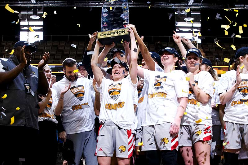 Women's basketball players hold up championship trophy while confetti falls from the ceiling.