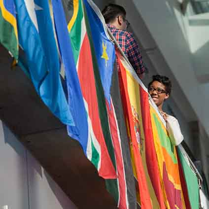 Students in the IUPUI Campus Center, standing in front of international flags