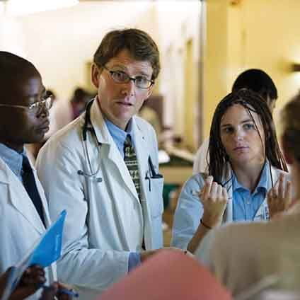 A group of medical students consult with a doctor