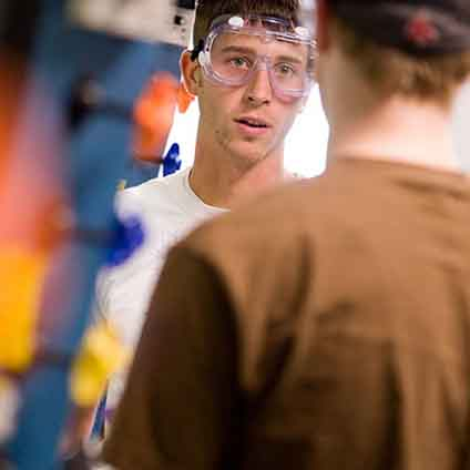 Engineering students wearing safety goggles in a lab environment