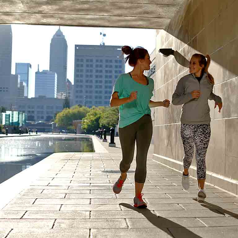 Two female runners jog along the Indianapolis White River Canal with the skyline behind them