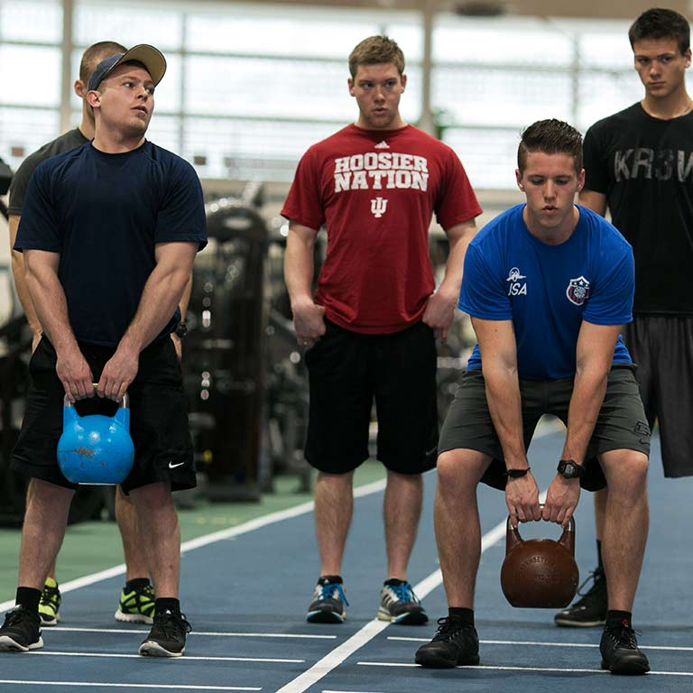 A group of men workout using kettle balls