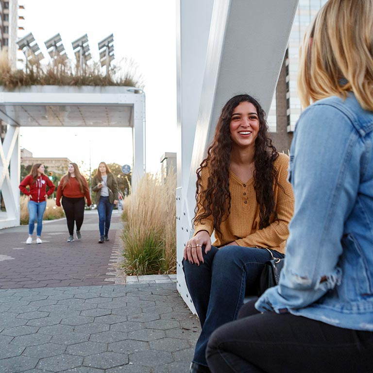 Two students sit on a metal sculpture while three girls walk in the background.