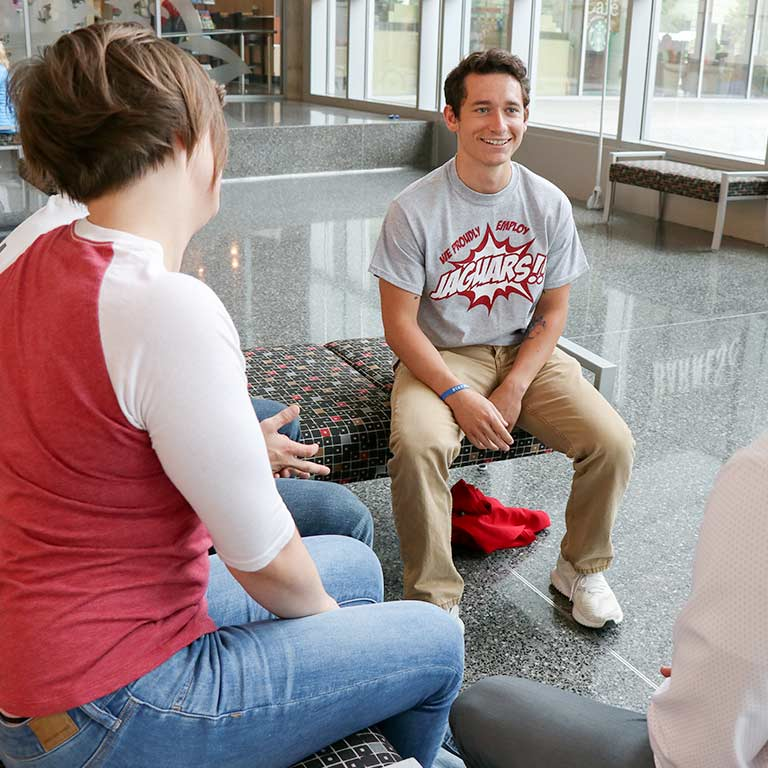 A male student sits and smiles with a group of friends in the campus center.