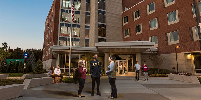 Multiple students talk outside of the new North Hall residences.