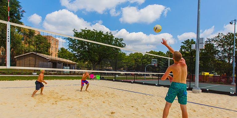 Students play beach volleyball on campus.