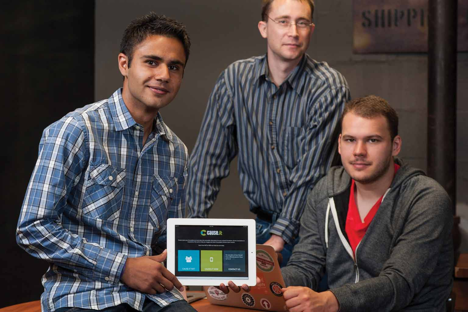 The three creators of the Cause.It app pose with an iPad