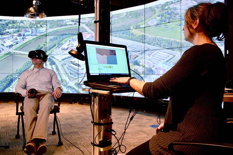 A person with virtual reality goggles sits in a chair while a person with a computer in front of them looks on.