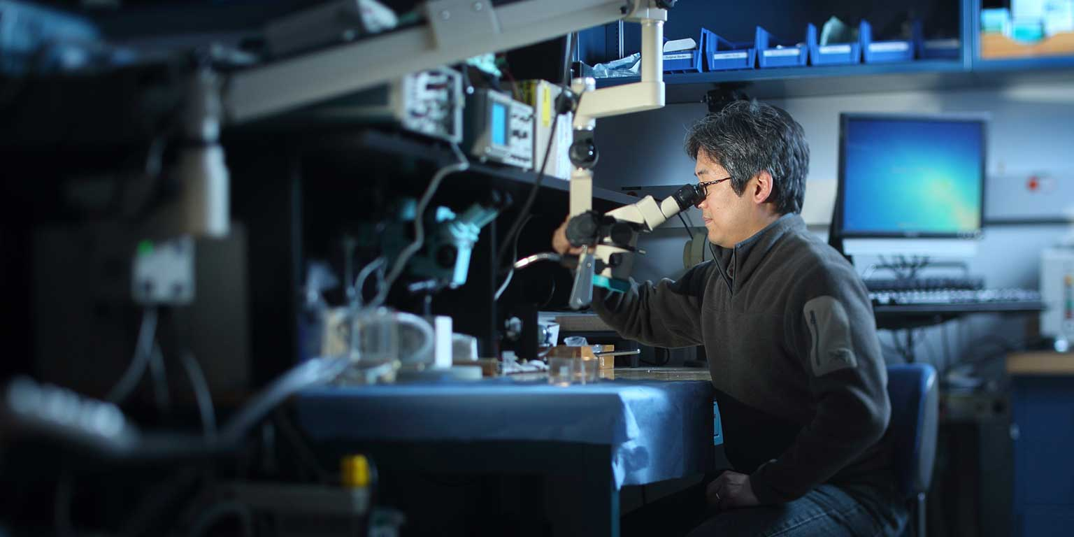 Male researcher looks into a microscope in a dimly lit room
